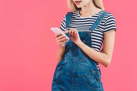 Photo pour Vue partielle de la femme en utilisant un smartphone isolé sur rose - image libre de droit