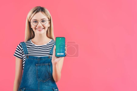 portrait of smiling woman in eyeglasses showing smartphone with twitter logo isolated on pink