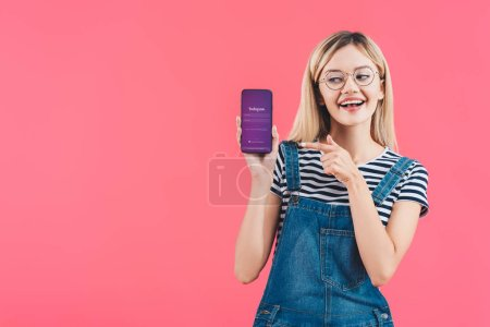 portrait of smiling woman in eyeglasses pointing at smartphone with instagram sign isolated on pink