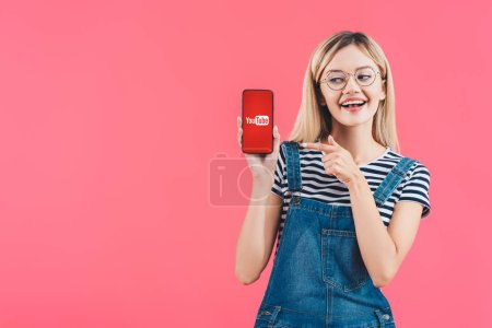 portrait of smiling woman in eyeglasses pointing at smartphone with youtube sign isolated on pink
