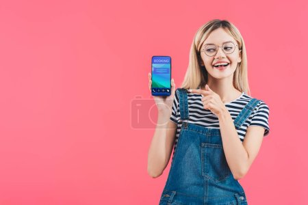 Photo for Portrait of smiling woman in eyeglasses pointing at smartphone with booking sign isolated on pink - Royalty Free Image