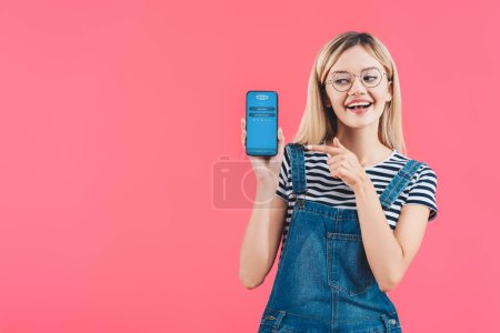 portrait of smiling woman in eyeglasses pointing at smartphone with skype logo isolated on pink
