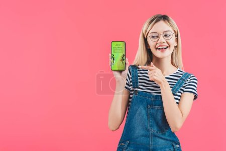 portrait of smiling woman in eyeglasses pointing at smartphone with best shopping sign isolated on pink