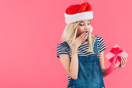 portrait of shocked woman in santa claus hat holding gift isolated on pink