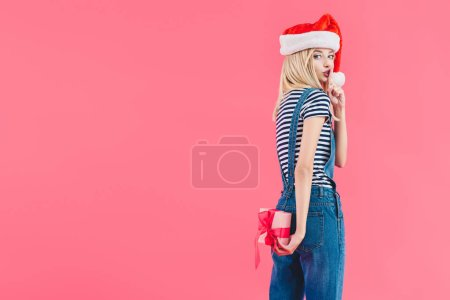 side view of woman in santa claus hat with gift showing silence sign isolated on pink