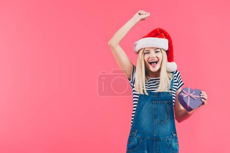 portrait of happy woman in santa claus hat with heart shaped gift isolated on pink