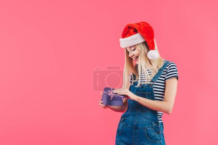smiling young woman in santa claus hat with heart shaped gift isolated on pink