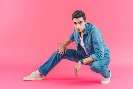 stylish man posing in denim clothes on pink background