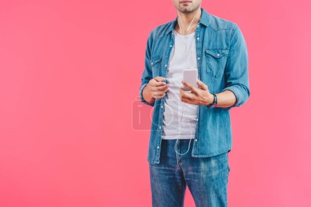 cropped shot of man with smartphone listening music in earphones isolated on pink