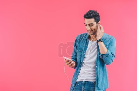 Photo for Portrait of smiling man with smartphone listening music in earphones isolated on pink - Royalty Free Image
