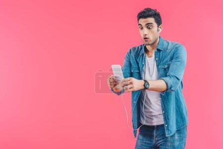 Photo pour Portrait de l'homme choqué dans les écouteurs regardant smartphone dans les mains isolées sur rose - image libre de droit