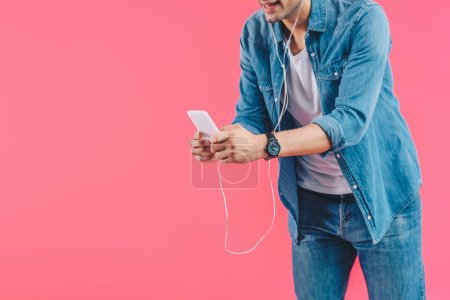partial view of man in earphones with smartphone isolated on pink