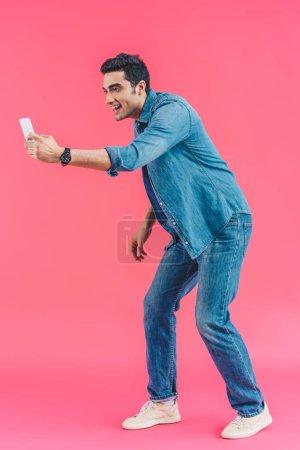 Foto de Vista lateral de hombre alegre tomando foto en smartphone sobre fondo rosa - Imagen libre de derechos