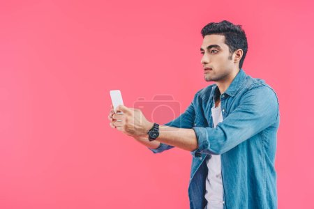 portrait of man taking selfie on smartphone isolated on pink