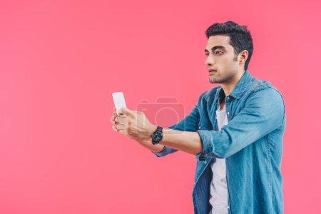 Photo pour Portrait d'homme prenant selfie sur smartphone isolé sur rose - image libre de droit