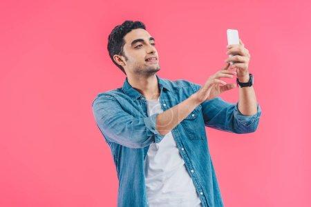 Photo pour Portrait de jeune homme prenant selfie sur smartphone isolé sur rose - image libre de droit