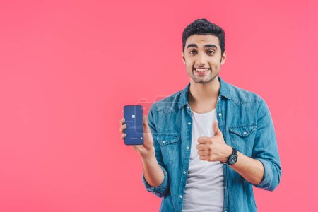 happy young man doing thumb up gesture and showing smartphone with facebook website isolated on pink
