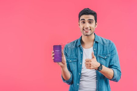 smiling young man doing thumb up gesture and showing smartphone with instagram website isolated on pink