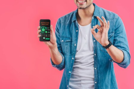 Photo for Partial view of young man doing ok sign and showing smartphone with marketing analysis  isolated on pink - Royalty Free Image