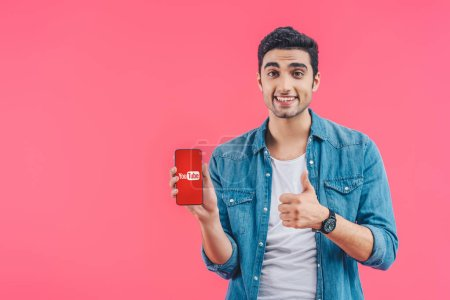 happy young man doing thumb up gesture and showing smartphone with youtube website isolated on pink
