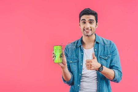 Photo pour Jeune homme souriant faisant geste pouce vers le haut et montrant smartphone avec les meilleurs achats isolés sur rose - image libre de droit