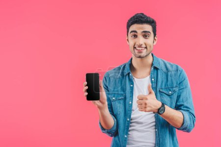 smiling young man doing thumb up gesture and showing smartphone with blank screen isolated on pink