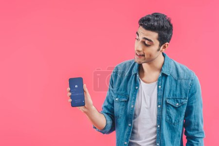 young man showing smartphone with facebook website isolated on pink