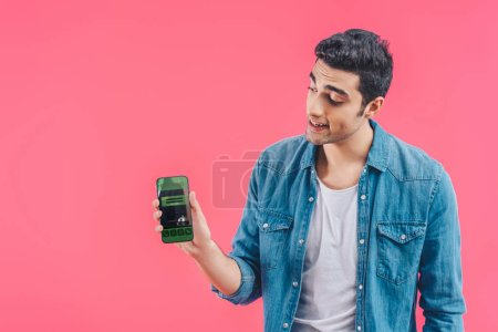 smiling young man showing smartphone with booking isolated on pink