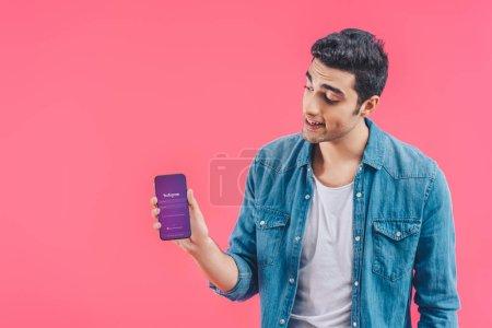 Photo pour Jeune homme montrant smartphone avec instagram site isolé sur rose - image libre de droit