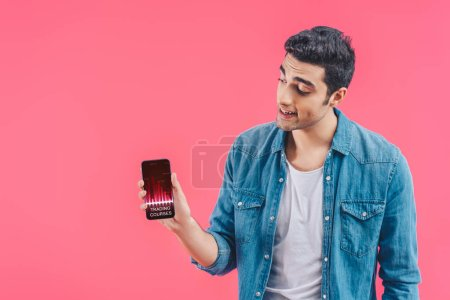 smiling young man showing smartphone with trading courses isolated on pink