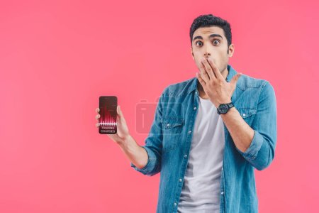 shocked young man covering mouth by hand and showing smartphone with trading courses isolated on pink