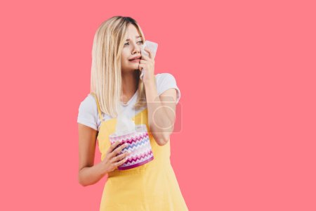 sad young woman with tissue box crying and wiping tears isolated on pink