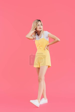 tense stylish woman touching hair and holding hand on waist isolated on pink