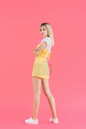 Photo for Irritated young woman with crossed arms looking at camera isolated on pink - Royalty Free Image