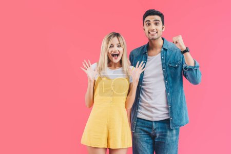 Photo for Excited young couple gesturing by hands and looking at camera isolated on pink - Royalty Free Image