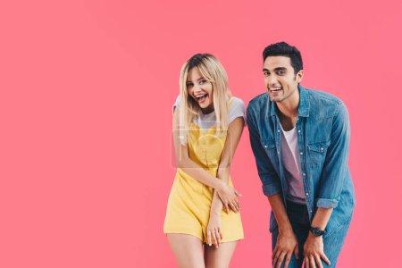 Photo pour Jeune couple caméra isolée sur rose en regardant en riant - image libre de droit