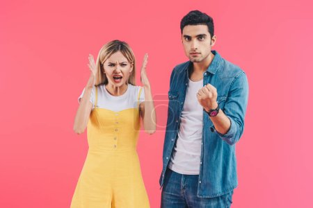 angry yelling woman gesturing by hands and her boyfriend threatening by fist isolated on pink