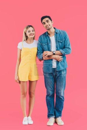 Photo pour Bonne humeur jeune couple main dans la main et en regardant caméra isolée sur rose - image libre de droit