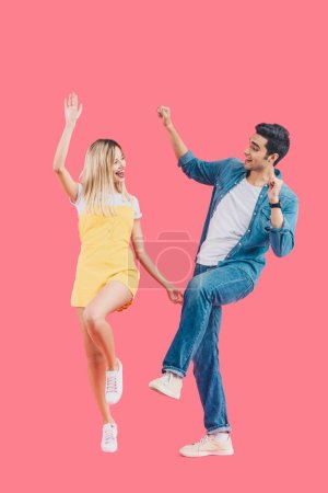 happy young couple looking at each other and dancing isolated on pink