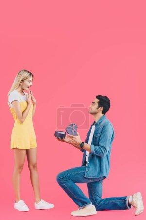 Photo pour Vue latérale de l'homme sur le genou plié faire la demande en mariage à petite amie surprise gestuelle par les mains isolées sur rose - image libre de droit