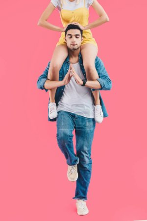 cropped image of woman sitting on shoulders of boyfriend while he meditating with closed eyes isolated on pink