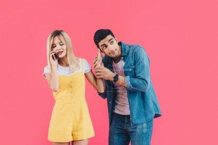 irritated young woman talking on smartphone and pushing away boyfriend isolated on pink