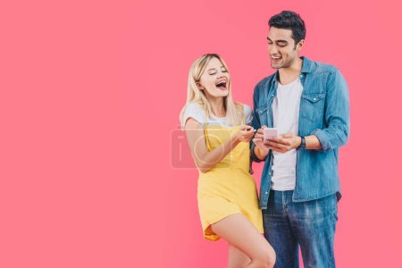 smiling man showing smartphone to laughing girlfriend isolated on pink