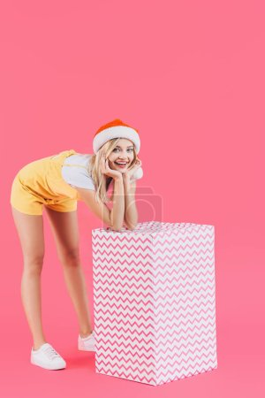 Photo for Smiling young woman in christmas hat standing with big gift box isolated on pink - Royalty Free Image