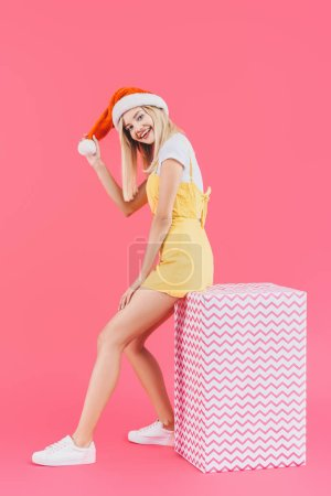 happy young woman in christmas hat sitting on big gift box isolated on pink