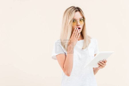 shocked stylish woman in eyeglasses covering mouth by hand and holding digital tablet isolated on beige