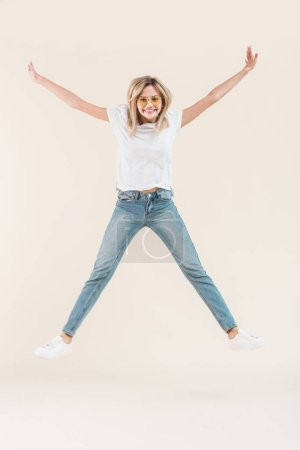 happy young woman in eyeglasses jumping with raised arms isolated on beige