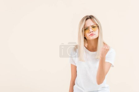 angry young woman in sunglasses shaking fist and looking at camera isolated on beige