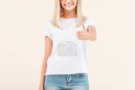 cropped shot of smiling young woman showing thumb up isolated on beige