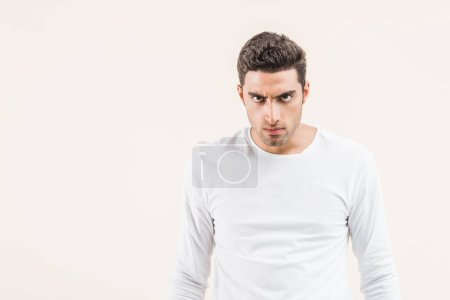 aggressive young man looking at camera isolated on beige